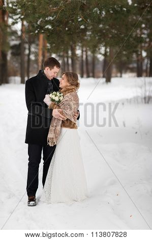 Young Couple Newlyweds Walking In A Winter Forest In The Snow.