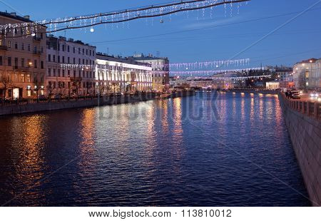 ST. PETERSBURG, RUSSIA - DECEMBER 27, 2015: Night view to the river Fontanka during New Year celebrations from the Anichkov bridge. The river is the border of parade buildings of St. Petersburg