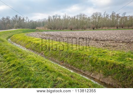 Curved Ditch Along A Plowed Field In The Autumn Season