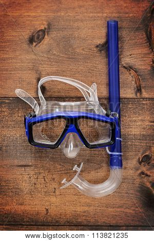 diving mask and snorkel on wood