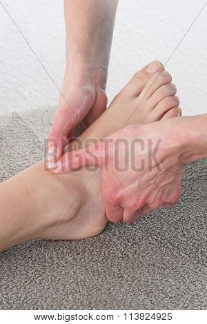 Macro Close Up Of Female Hands Massaging Girls Foot.