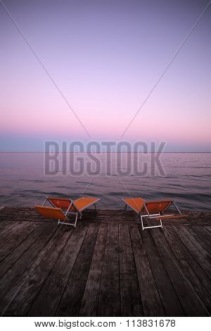 Chaise Lounges On Wooden Pier