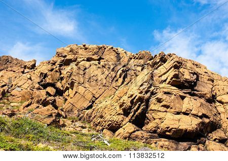 Large Irregular Cracked Rock Outcrop Against Sky