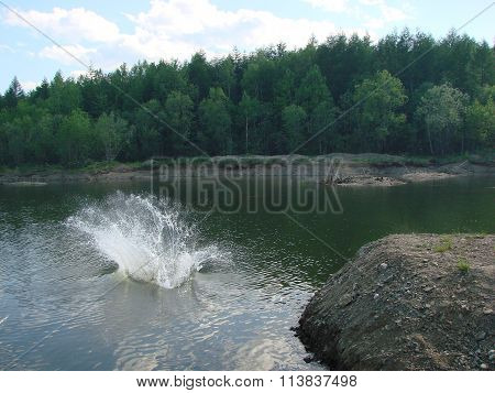The man jumping in water. It is a lot of water splashes. Landscape view of the river beach. ** Note: Visible grain at 100%, best at smaller sizes