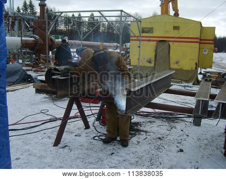 Russia, Yuzhno-Sakhalinsk - November 18, 2014: The worker is occupied with welding works. Two-Tauri welding connection of a design.