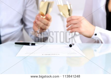 Close-up Image Of A  Contract . Two Colleagues Celebrate  Signing A Contract With Champagne