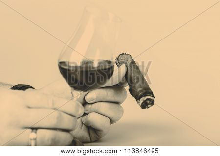 Old brandy or rum in glass and cigar in male hand on white background
