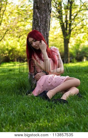 Young and beautiful ukrainian girl  with red hair sits under the tree in the park