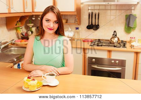 Woman With Coffee And Cake In Kitchen. Gluttony.