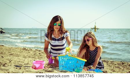 Family Mother And Daughter Having Fun On Beach.
