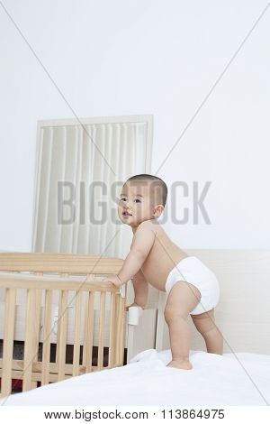 Cute Chinese Baby Boy Standing By His Crib