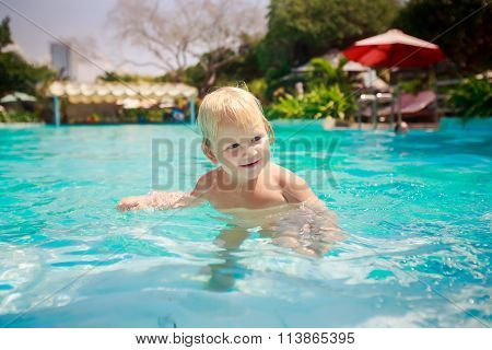 Small Blonde Girl Stands Looks Slyly In Shallow Water Of Pool