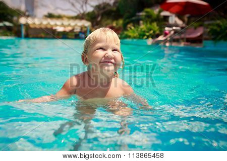 Small Blonde Girl Stands Screws Up Eyes In Shallow Pool Water