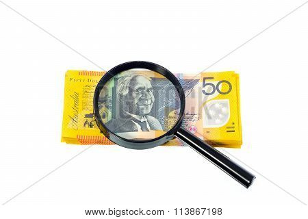 Australian Banknote Under A Magnifying Glass Is Being Inspected On White Background