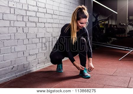 Attractive girl ties the laces on sneakers