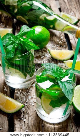 Freshly Made Mojito In Glass And The Bottle With Mint And Lime, Sugar And Rum. On A Wooden Table.