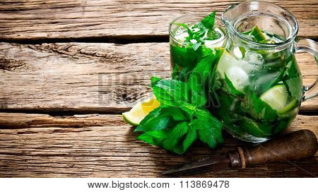 Cooked Cocktail Of Lime, Mint, Rum And Ice On Wooden Table . Top View