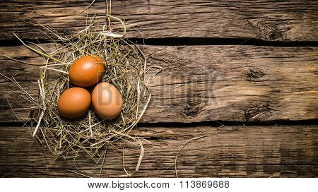 Eggs In The Hay . On Wooden Table.