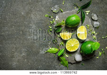Lime Background. Slices Of Lime With Ice And Leaves On A Stone Stand .