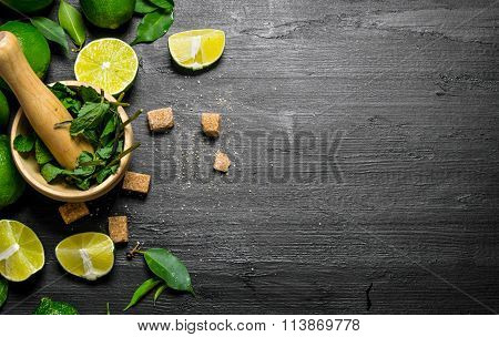 Lime Background. The Mortar With Mint, Sugar , Lime Slices And Leaves .