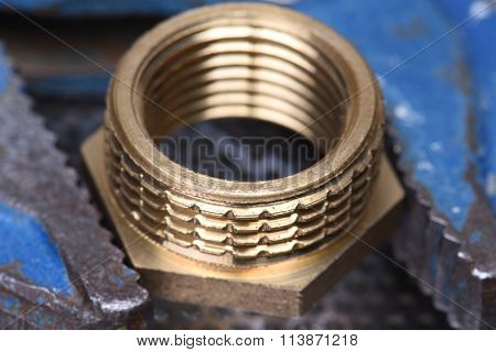 Closeup of brass threaded connector nipple with wrench