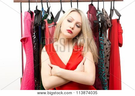 beautiful blond girl in a red dress in front of a clothes hanger. isolated on white background