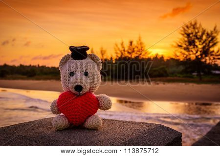 Teddy Bear With Red Heart Sitting Near The Beach At Sunset