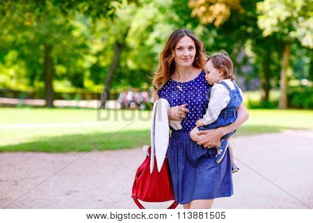 mother and her little daughter walking in summer park
