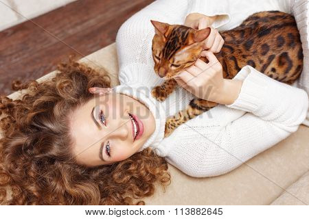 Girl Scratching Cat Lying On The Sofa. Hugs.