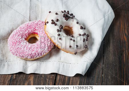 Sweet sugary donuts on rustic wooden kitchen table