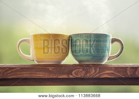 Mugs With A Hot Drink With Tea On A Wooden Stand Outdoors