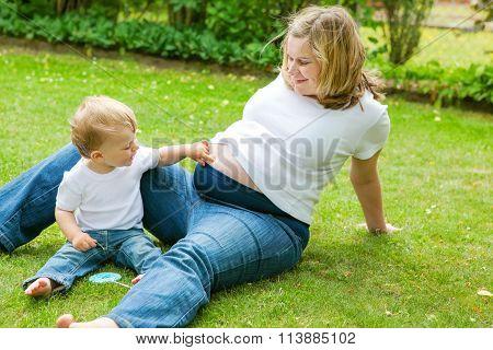 Pregnant woman and adorable little toddler son in garden.