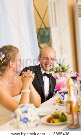 stylish bride and happy groom in the restaurant centerpiece reception having fun