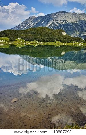 Landscape of Todorka Peak and reflection in Muratovo lake, Pirin Mountain
