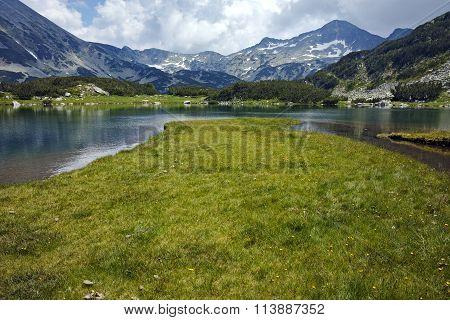 Clouds over Banderishki Chukar peak and reflection in Muratovo lake, Pirin Mountain