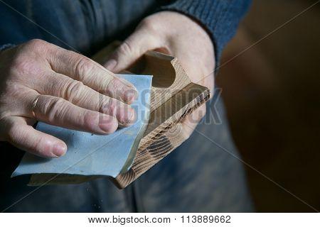 Man sandpaper grinds wood product