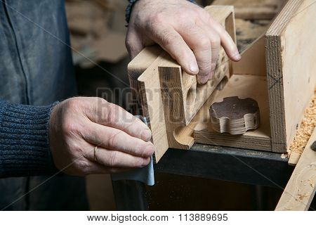 Man sandpaper grinds wood product in the shop