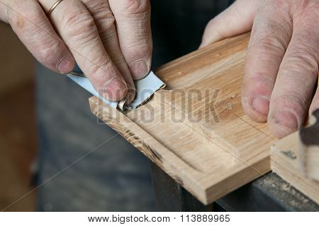 Men sandpaper grinds wood product in a workshop