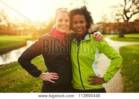 Two Female Athletes Hugging And Looking At Camera