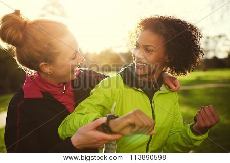 Two Female Athletes Smiling And Hugging After Workout In Park
