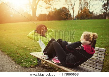 Two Female Athletes Doing Sit-ups On Bench In Park