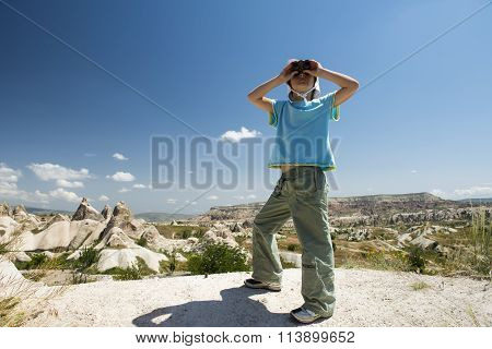Small girl with binocular in mountains