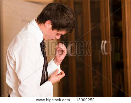 Businessman buttoning up white shirt. Groom preparing for wedding.