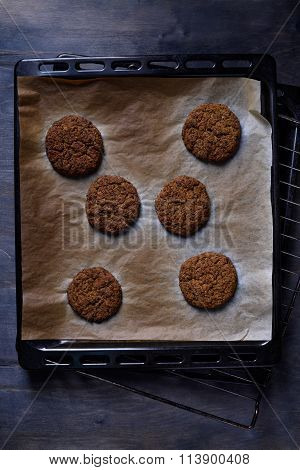 Vegetarian falafel chickpea patties on backing tray with green onion, wood background. Copy space, t