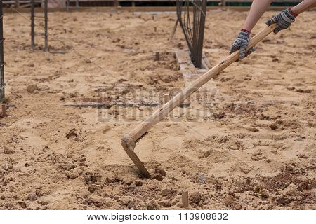 Digging The Soil With A Hoe At Construction