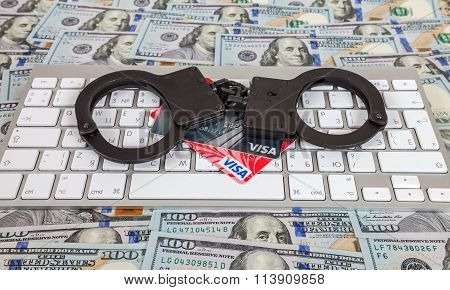 Steel Handcuffs And Credit Cards Lying On A Computer Keyboard On The Background Of Dollars