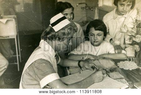 KATOWICE, POLAND, CIRCA 1939: Vintage photo of nurse working with children