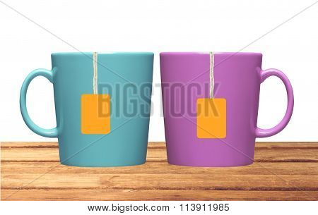 Two Cups And Tea Bags With Orange Label On Table Isolated On White
