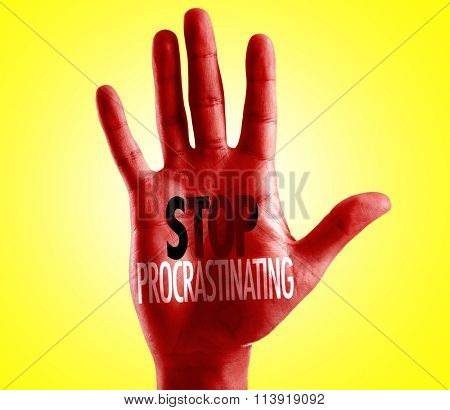 Stop Procrastinating written on hand with yellow background