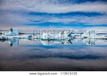 Ice magnificence. Floating ice and clouds are reflected in smooth mirror water of the Ice lagoon. Iceland